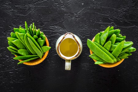 Green pea pods in bowls near jug of oil on black background top view.