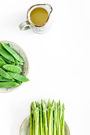 Fresh green pea pods and sprout of asparagus on white background top view. 版權商用圖片