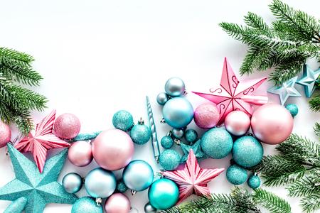 クリスマスの装飾パターン。ピンクとブルーの星と白い背景の上の松の枝に近いボール平面図です。