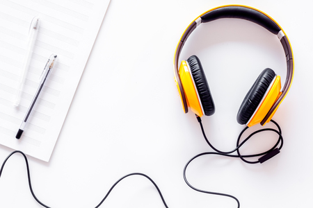 Compose music. Headphones and music notes on white background top view.