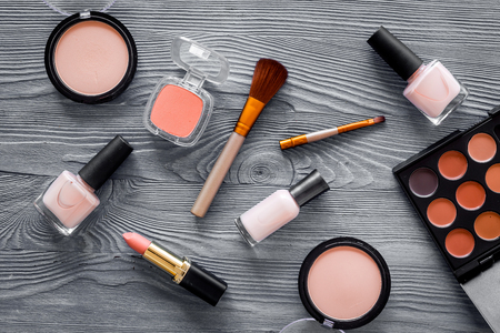 Cosmetics set with beige and nude tones for natural makeup on grey wooden background top view.