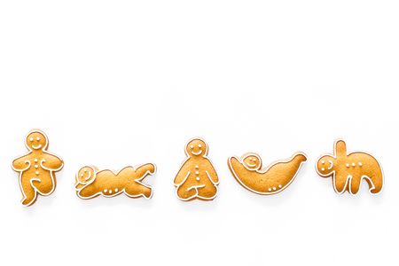 Gingerbread cookies in shape of yoga asanas on white background top view. Stock Photo