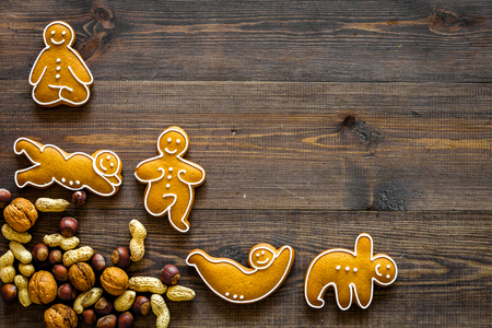 Healthy food for sportsman. Cookies in shape of yoga asanas near nuts on dark wooden background top view.