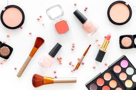 Cosmetics set with beige and nude tones for natural makeup on white background top view.