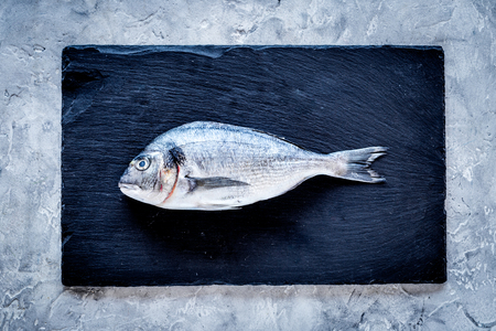 Fresh dorado fish ready to cook on black and grey background top view.
