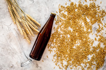 Grains of malting barley near beer bottle on grey background top view copyspace Stock Photo - 87874940