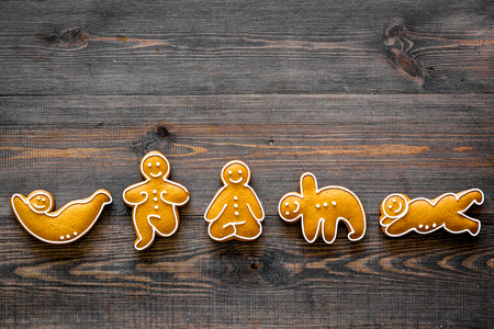 Gingerbread cookies in shape of yoga asanas on dark wooden background top view copyspace