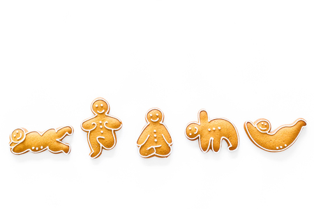 Gingerbread cookies in shape of yoga asanas on white background top view copyspace
