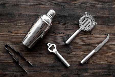 Instruments bartender. Shaker, strainer on wooden background top view