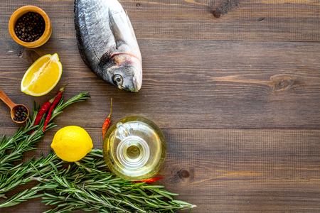 Mediterranian cuisine. Dorado with rosemary, pepper, chili, lemon on wooden background top view copyspace