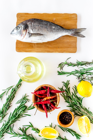 Preparing dorado with spices rosemary, pepper, chili, lemon. White background top view