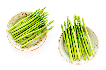 Sprout of fresh asparagus on plate on white background top view