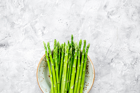 Sprouts of fresh asparagus on grey stone background top view copyspace