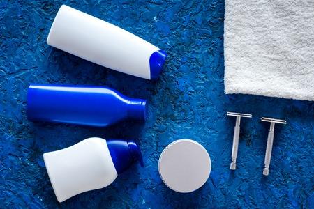 Herencosmetica voor haarverzorging en scheren. Shampoo, gel, scheermes, was op blauwe hoogste mening als achtergrond copyspace Stockfoto