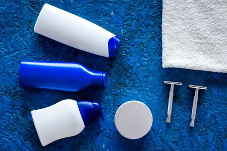 Mens cosmetics for hair care and shaving. Shampoo, gel, razor, wax on blue background top view copyspace Reklamní fotografie