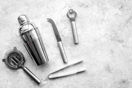 Bar tools for making cocktails on grey stone background top view.