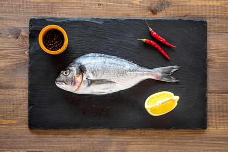 Fresh dorado fish ready to cook on black desk on wooden background top view.