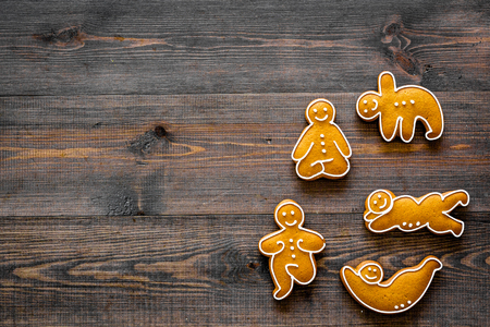 Gingerbread cookies in shape of yoga asanas on dark wooden background top view.