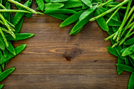 Fresh pea pods on dark wooden background top view.