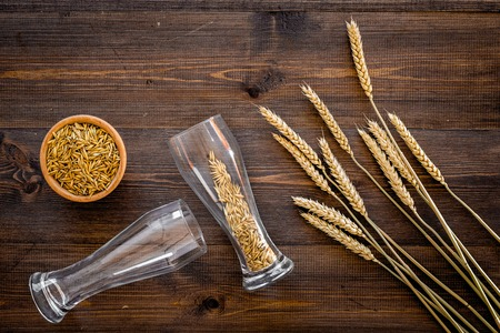 Ingredients for beer. Malting barley in beer glass on wooden background top view.