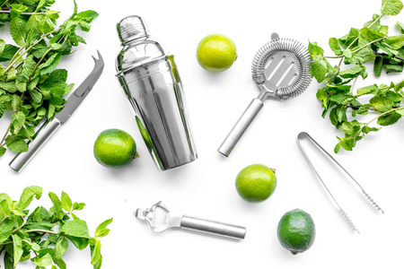 Make mojito cocktail with lime and peppermint in shaker. White background top view. Stock Photo