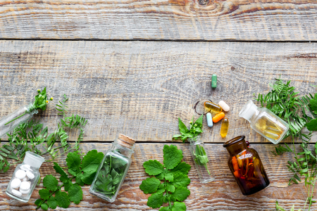Healing herbs. Fresh leaves, bottles and pills on wooden background top view copyspace