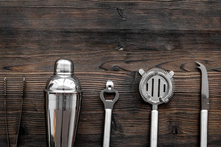 Instruments bartender. Shaker, strainer on wooden background top view.