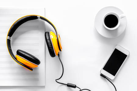 Worktable of composer today. Headphones, phone, music notes on white background top view. Stock Photo