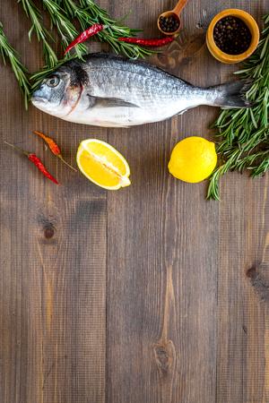 Mediterranian cuisine. Dorado with rosemary, pepper, chili, lemon on wooden background top view. Stock fotó - 87873593