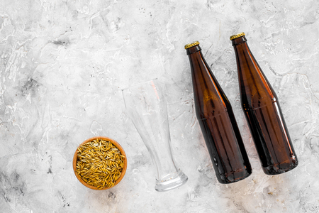 Ingredients for beer. Malting barley near beer glasses and bottle on grey background top view. Stock Photo - 87873726