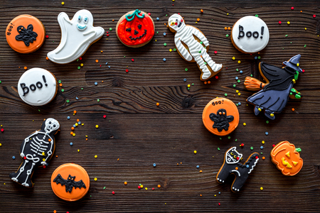 Cook halloween gingerbread cookies with witch, skeleton, ghost. Wooden background top view. Stock Photo