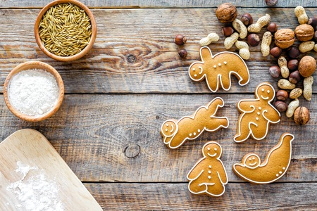 ration: Healthy food for sportsman. Cookies in shape of yoga asanas near nuts on wooden desk background top view copyspace