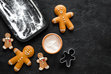 Make gingerbread cookies for new year 2018. Sweets near baking sheet on black background top view. Stockfoto