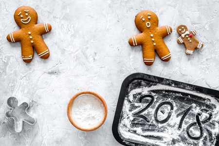 Cook gingerbread for new year 2018. Gingerbread man, flour on stone background top view.