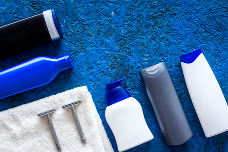 Mens cosmetics for hair care and shaving. Shampoo, gel, razor, wax on blue background top view. Stock Photo