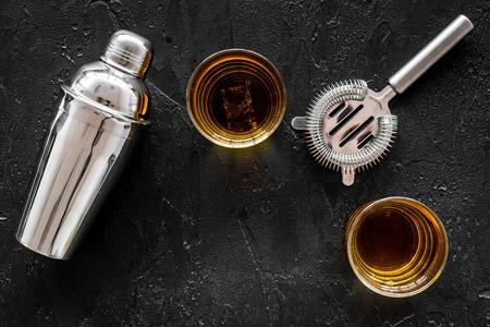 Ontsproten van whisky met ijs en barmannenmateriaal op zwarte lijst achtergrond hoogste meningsruimte voor tekst Stockfoto