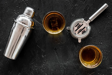 Shot of whiskey with ice and barmen equipment on black table background top view space for text Zdjęcie Seryjne
