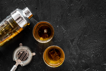 Shot of whiskey with ice and barmen equipment on black table background top view space for text Stock Photo