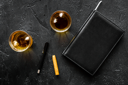 Man set. Whiskey with ice, cigar and notebook on black bar background top view copyspace Stock Photo