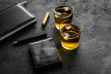 Man set. Whiskey with ice, cigar, wallet and notebook on black bar background