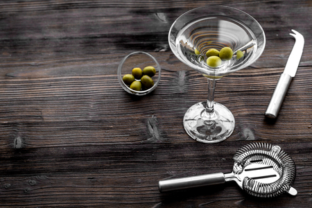Make martini cocktails. Glass with beverage, olives and utensils on dark wooden background top view.