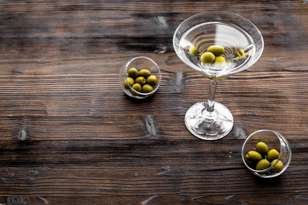 Martini cocktail in glass with olives at the bottom on dark wooden background top view. Stock Photo