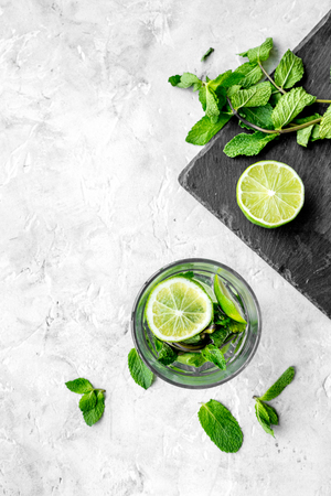 Glass of mojito, lime, mint on grey stone background top view. Stock Photo