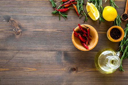 Spices rosemary, pepper, chili, lemon for cooking sea fish Wooden background top view. Stock Photo