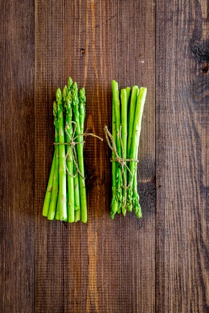 Bunches of fresh asparagus sprouts on dark wooden background top view. Imagens