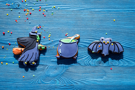 Cook halloween gingerbread cookies with witch, bat. Blue background top view. Stock Photo