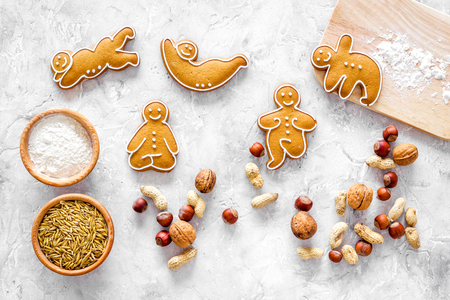 Healthy food for sportsman. Cookies in shape of yoga asanas near nuts on stone table background top view.