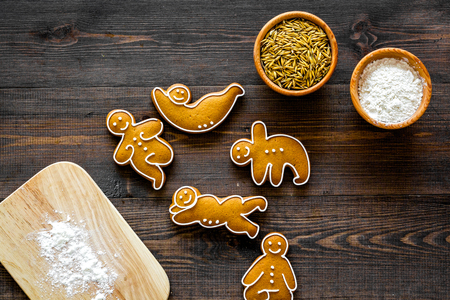 Make gluten free healthy food. Yoga asanas cookies near desk, flour and wheat on dark wooden background top view.