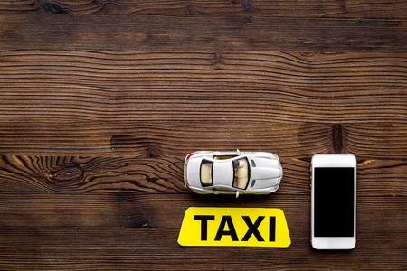Online order a taxi with mobile app and car model on wooden table background top view mockup Stock Photo