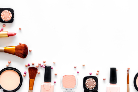 Pattern with cosmetics set with beige and nude colors on white background top view.